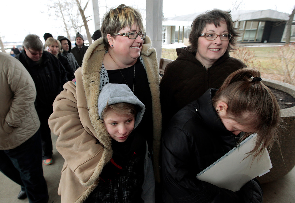Description of . Jenny Stanczyk, rear at left, and Cheryl Pine, rear at right, wait in line to apply for a marriage license at the Oakland County Clerks office with Maria , and Nina Stanczyk , front left and right, in Pontiac, Mich., Saturday, March 22, 2014. A federal judge has struck down Michigan's ban on gay marriage Friday the latest in a series of decisions overturning similar laws across the U.S. Some counties plan to issue marriage licenses to same-sex couples Saturday, less than 24 hours after a judge overturned Michigan's ban on gay marriage. (AP Photo/Paul Sancya)