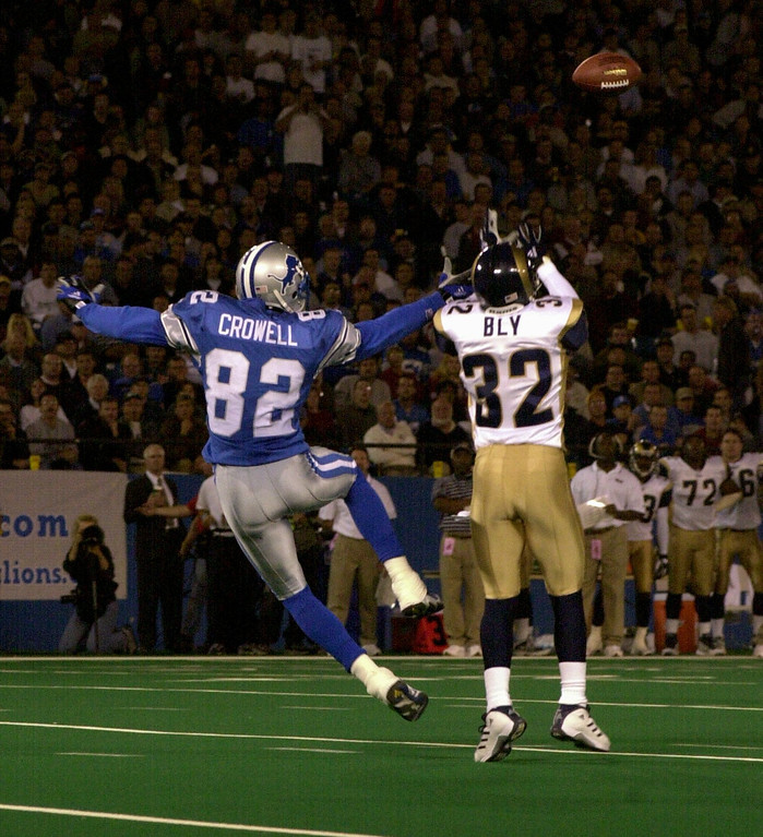. Detroit Lions wide receiver Germane Crowell (left, #82) is about to have the ball intercepted by St. Louis Rams cornerback Dre Bly (#32) during second quarter action in a game played at the Pontiac Silverdome in Pontiac, Mich., Monday, October 8, 2001.