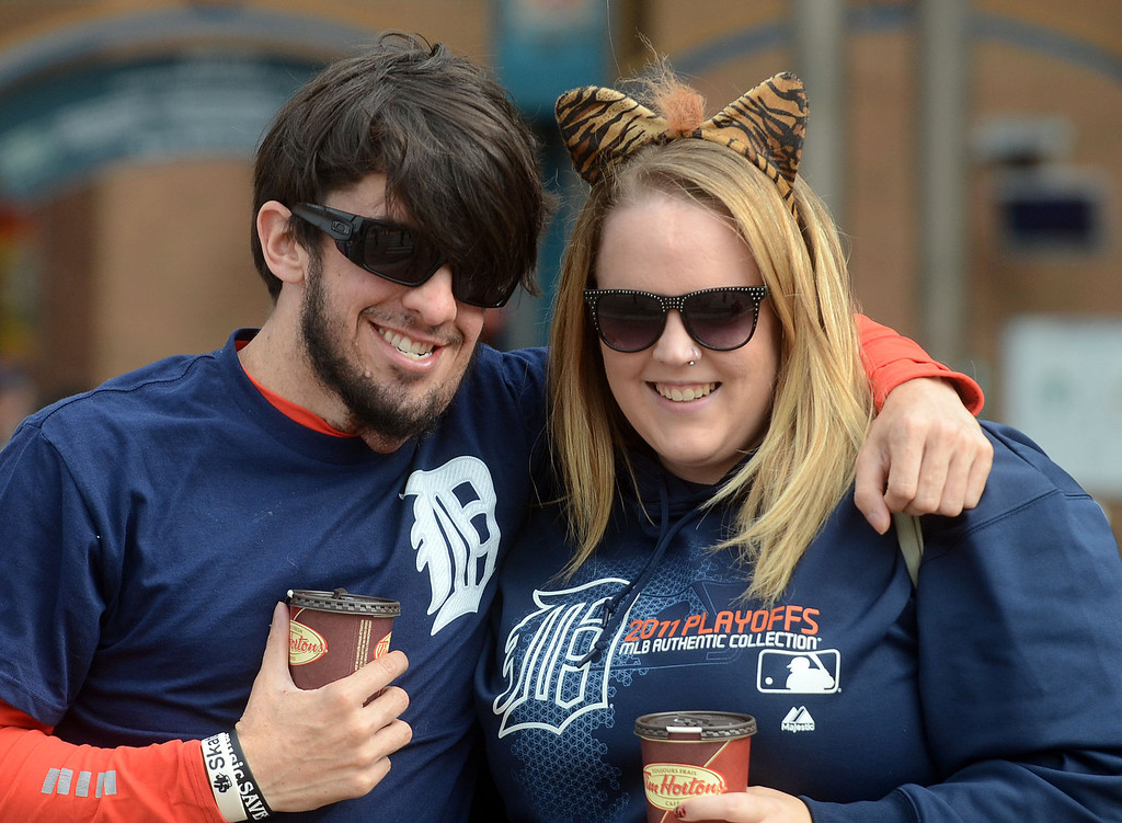 Description of . Michael Beneteau and Mandie Armstrong, of Windsor, have their picture taken before heading into Comerica Park for the start of Game 3 of the ALDS between the Tigers and Oakland A's, Monday October 7, 2013. (Oakland Press Photo:Vaughn Gurganian)