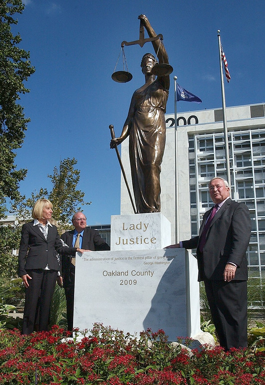 Description of . (from left) Wendy Potts, Oakland County Circuit Chief Judge, Bill Bullard, Chairman, Oakland County Board of Commissioners and L. Brooks Patterson, Oakland County Executive, unveil the new Lady Justice statue after it was dedicated outside the south entrance of the Oakland County Circuit Court Building in Pontiac.