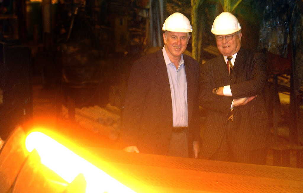 Description of . (f.left) Russell Maier, President & CEO and L. Brooks Patterson, Oakland County Executive, watch a super heated tube roll off the line during a tour of the Michigan Seamless Tube company in South Lyon, Thursday November 4, 2004.