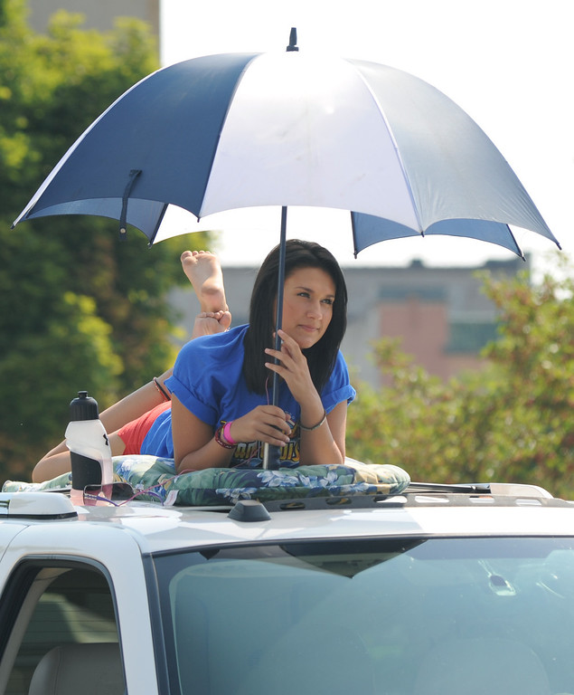 Description of . Kristy Willauer, age 15, of Macomb Township, Mich., keeps cool under an umbrella on top of her family's vehicle, as she watches the Dream Cruise, Saturday, August 15, 2009, in Pontiac, Mich.  (The Oakland Press/Jose Juarez)