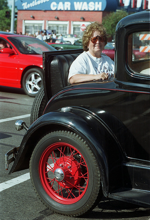 Description of . Arbie Phillips smiles from the rumble seat of this 1930 Model A as she heads south on Woodward during the Dream Cruise 2000 saturday afternoon.