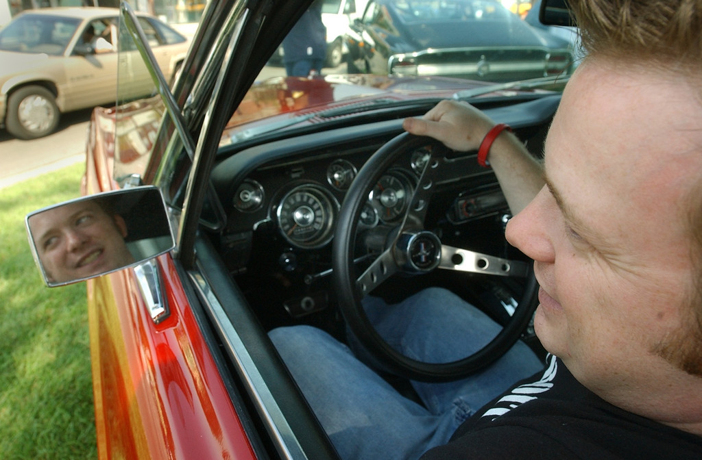 Description of . Nate Lucas, of Madison Heights, sits in his 1967 Mustang GTA fastback during a press conference kicking off the 2005 Woodward Dream Cruise in Ferndale, Tuesday August 16, 2005.