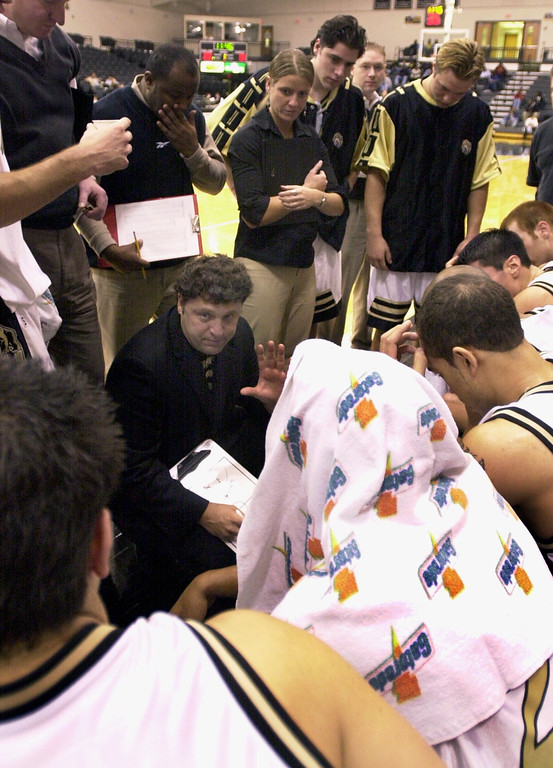 Description of . Oakland University mens basketball head coach Greg Kampe, bottom left, gives instructions to his team during a timeout as they played the Premier All-Stars AAU, during first half action, Saturday, November 10, 2001, at the O'rena in Rochester Hills, Mich.