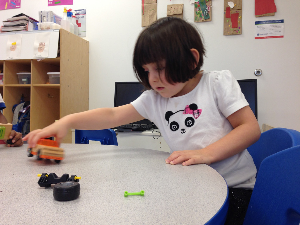 Description of . A preschooler is testing out a toy car with different parts to analyze it during a toy testing session at the Goddard School in Canton.