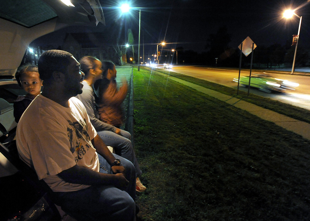 Description of . Robert Cato, foreground, of Pontiac, Mich., and his family (L-R): Cianna Cato, age 2; Janell Cato; and Halaya Cato, age 9, watch cars begin their turn on the Loop, along northbound Woodward Avenue.  The Cato family, who watched from the back of their vehicle in the parking lot of St. Vincent De Paul Catholic Church, watched cars from about 8:30 pm to 10:30 pm.  The reason they came out to watch the cars three days before the actual Dream Cruise was because, according to Robert, it was Halaya's idea to watch the cruisers at night.  Halaya also wanted to count how many