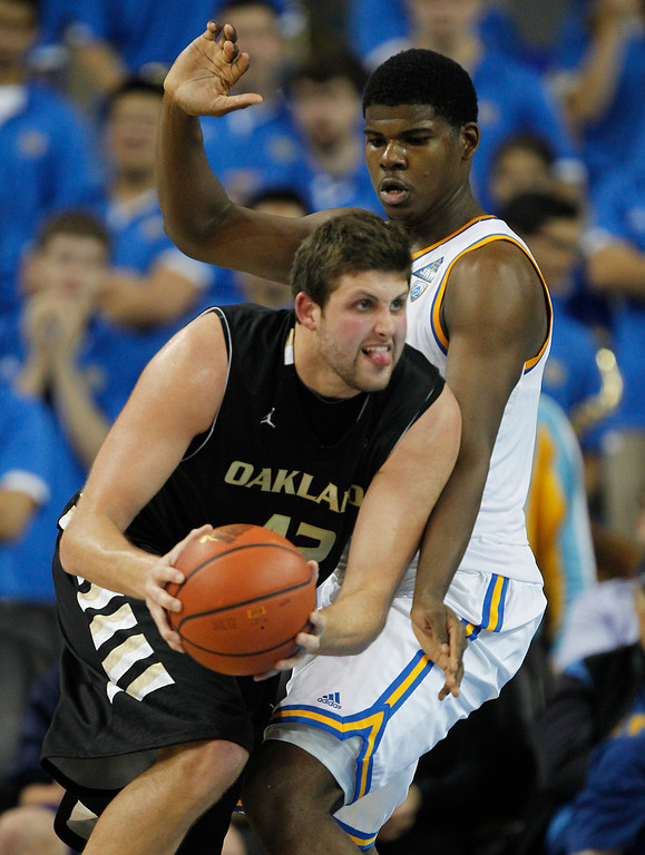 Description of . Oakland center Corey Petros, left, looks to pass the ball as UCLA center Tony Parker defends during the second half of an NCAA college basketball game Tuesday, Nov. 12, 2013, in Los Angeles. UCLA won 91-60. (AP Photo/Alex Gallardo)