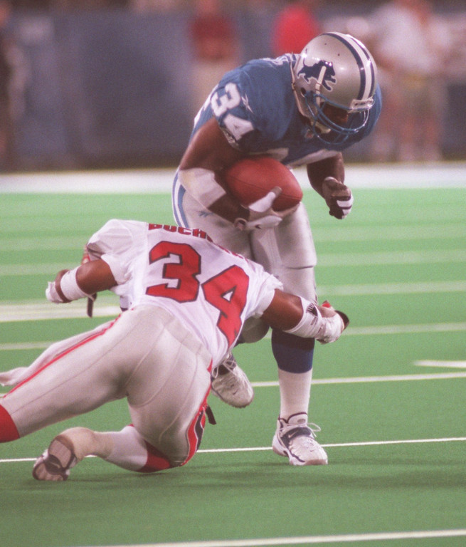 . Detroit Lions running back Ron Rivers (right,#34) runs for yardage as Atlanta Falcons cornerback Ray Buchanan tackles him, during second quarter action at the Pontiac Silverdome, Friday, August 14, 1998.
