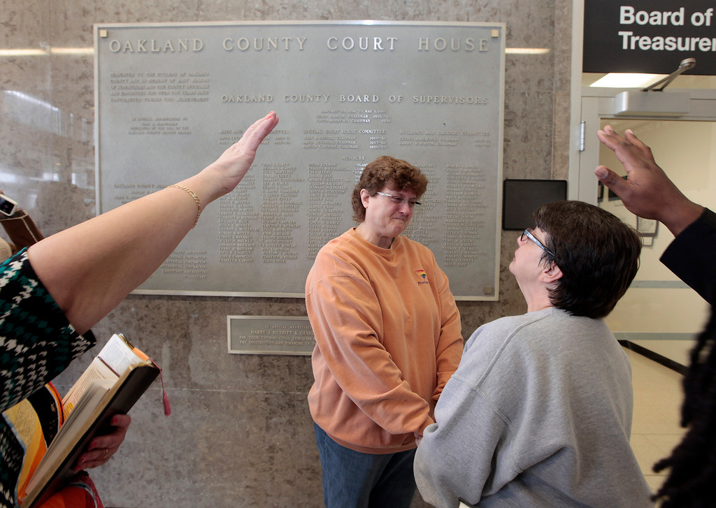 Description of . Cathy Fisher, left, and Laurie Fisher are married at the Oakland County Courthouse in Pontiac, Mich., Saturday, March 22, 2014. A federal judge has struck down Michigan's ban on gay marriage Friday the latest in a series of decisions overturning similar laws across the U.S. Some counties plan to issue marriage licenses to same-sex couples Saturday, less than 24 hours after a judge overturned Michigan's ban on gay marriage. (AP Photo/Paul Sancya)