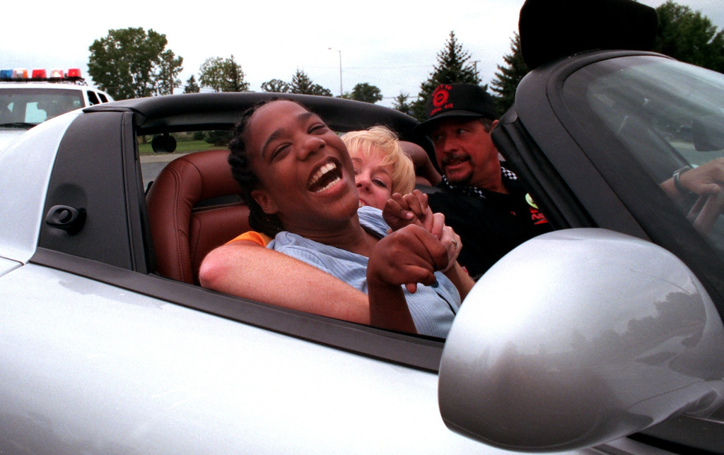 Description of . Siakara Cooper,19, (foreground), sits on her teacher Kathy Wells' lap as she cruises around the parking lot in a Dodge Viper at the Kennedy Dream Cruise.  The kids from the center were given the opportunity to take rides in three different cars around the parking lot following a 50s and 60s dance at the Kennedy Center.