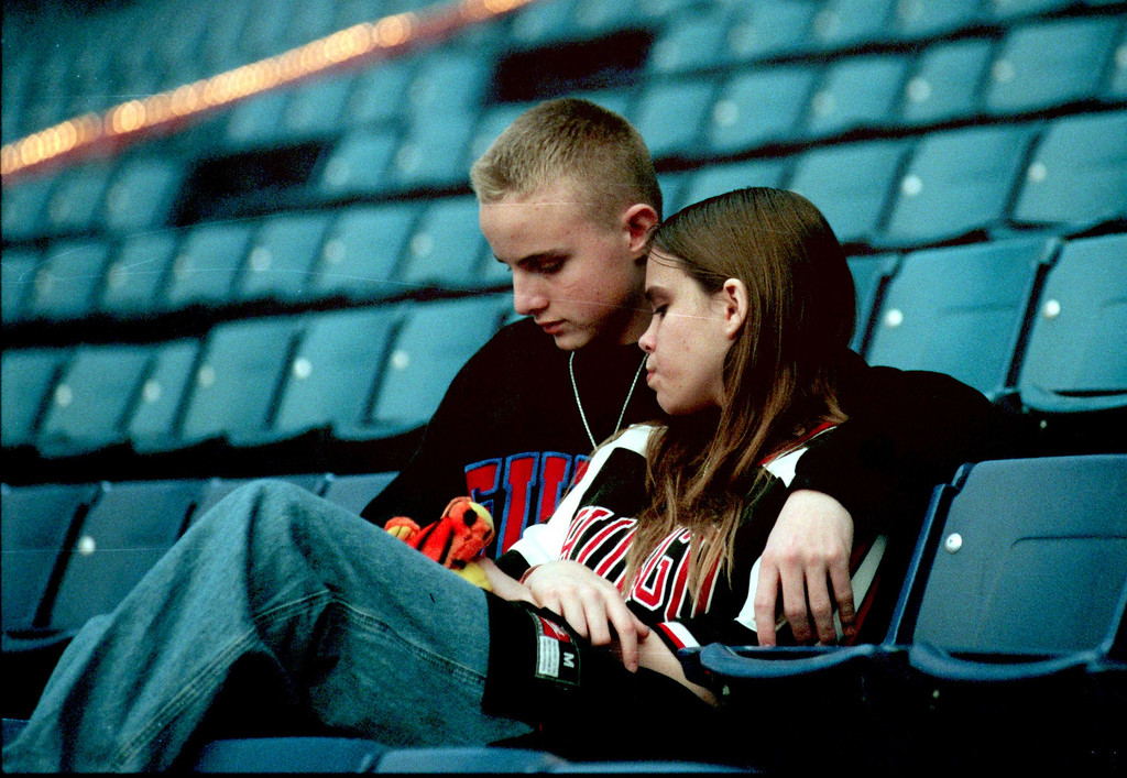 Description of . Taking a break from the hoopla of the Winter Carnival, Ricky Flynn and Crystal McCaulley share a quiet moment in the empty Silverdome seats.
