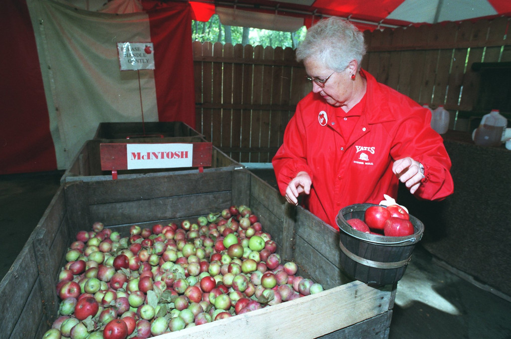 Description of . Yates Cider Mill in Rochester Hills. Joyce Breederland of Shelby Twp. mans the apple tent. at the Cider Mill, filling a basket with McIntosh apples.