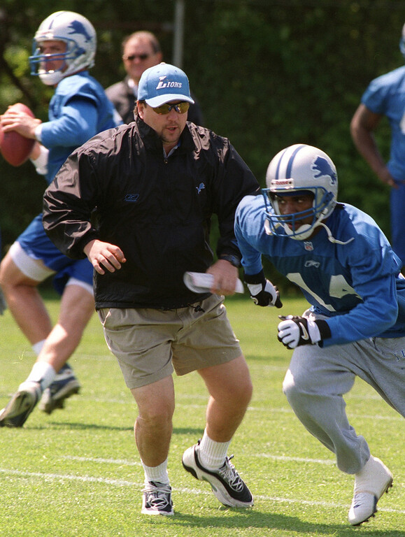 . Detroit Lion new head coach Marty Mornhinweg gets into the play as receiver Andre Rone (14) runs a route during Wednesday\'s Lions minicamp held at the Pontiac Silverdome.