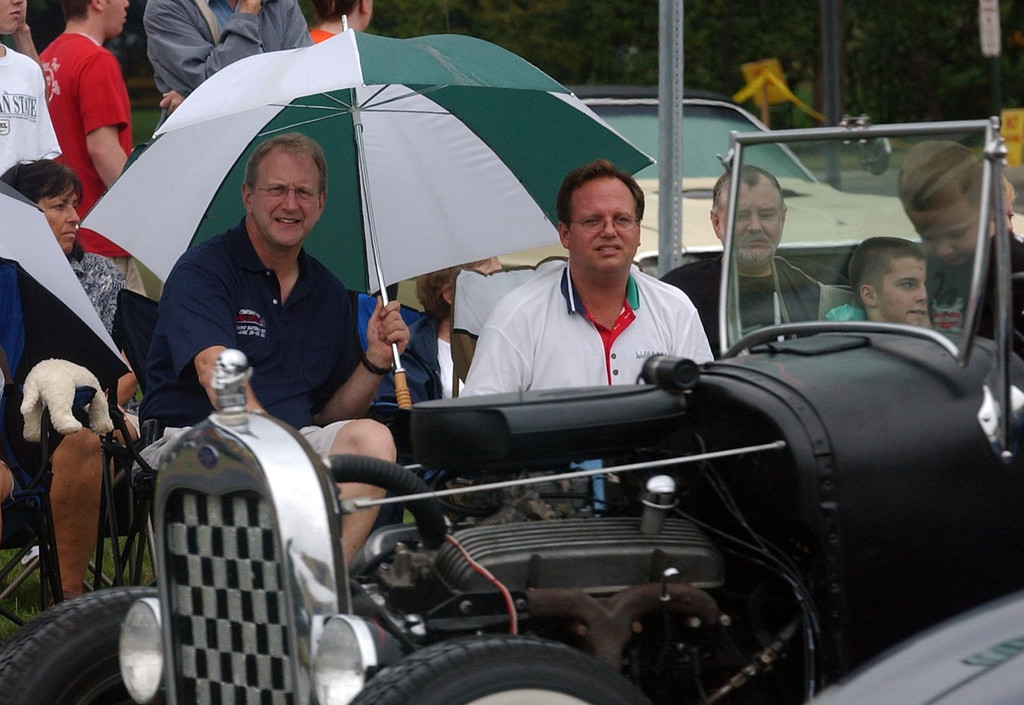 Description of . (from left) Dick Roth, of Shelby Twp. and Dean Didion, of Clarkston, stay dry while watching the classic cars cruise Woodward Ave. in Royal Oak during the 2006 Woodward Dream Cruise.