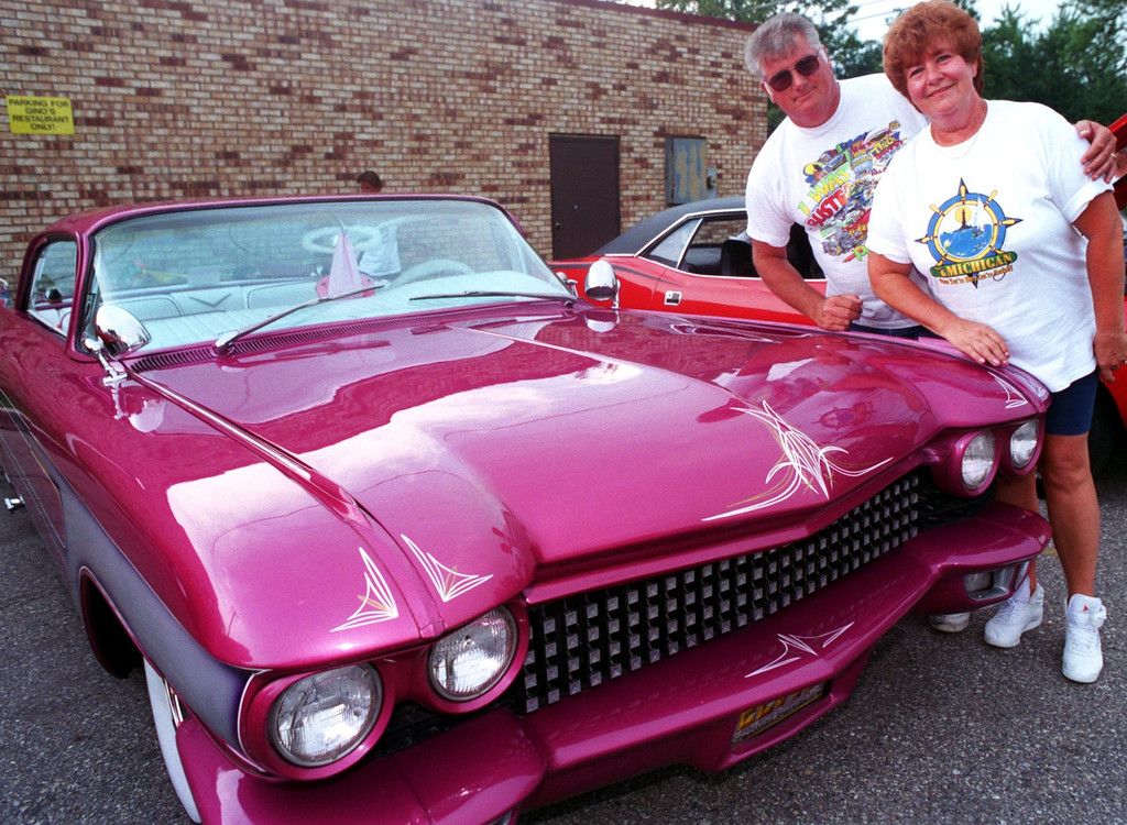 Description of . Pontiac\'s Lloyd and Kathy Berry showed off their 1960 pink and purple Caddy at the Pre-Dream Cruise in the parking lot of Gino\'s Restaurant in Keego Harbor.