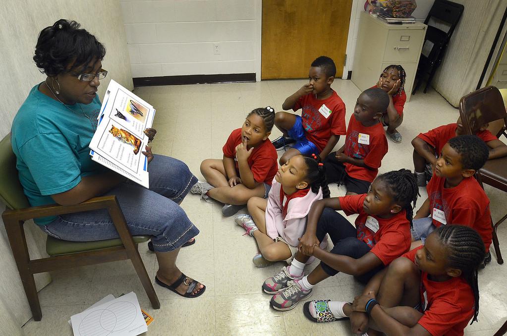 Description of . Jennifer Graham, of Detroit, reads to kids during the free Camp Hosanna at New Bethel Missionary Baptist Church in Pontiac, Monday July 22, 2013. (Oakland Press Photo:Vaughn Gurganian)