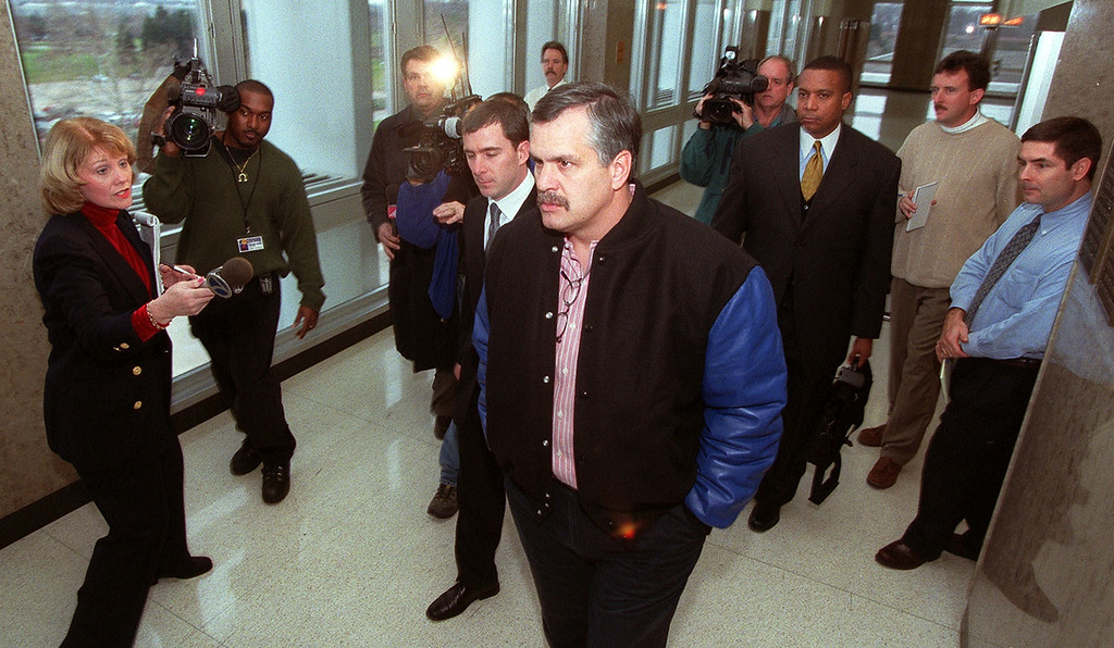 . Detroit Lions president Matt Millen, center, makes his past the reporters in the hallway of Oakland County Circuit Court in Pontiac Wednesday afternoon. The Lions and the city of Pontiac are disputing their lease at the Silverdome in Pontiac. Judge Fred Mester ordered both side into court today to try to resolive this matter before it goes to trial.
