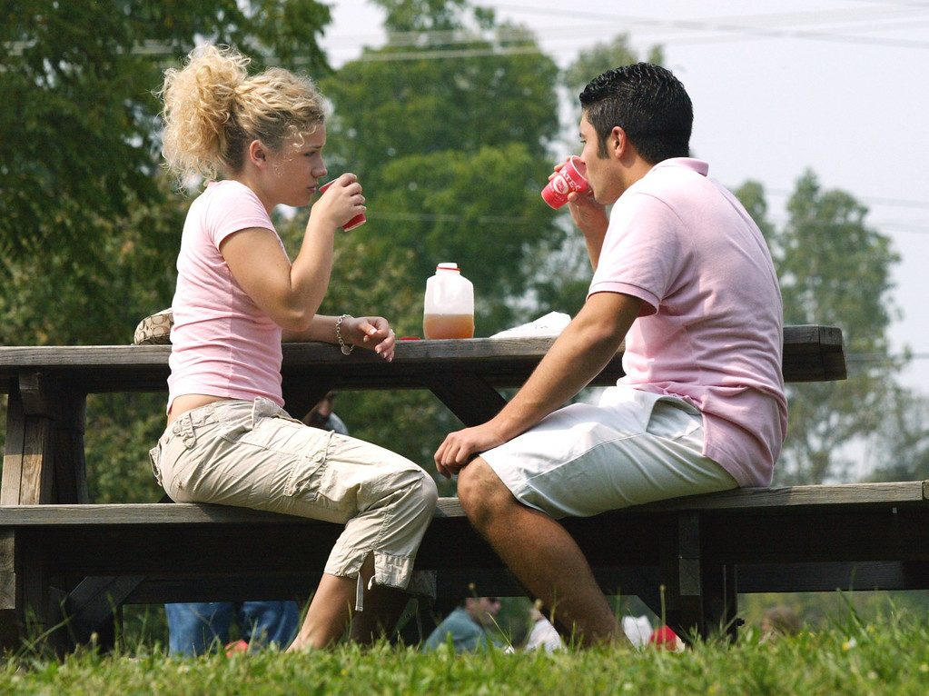 Description of . Meghan Dehring, 18, drinks cider with her boyfriend Giovanni Bugli, 19, (both of Shelby Township) at Yates Cider Mill.  Photographed Sunday, September 4, 2004.