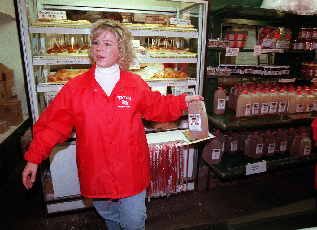 Description of . Working as fast as she can behind the counter to keep up with a long line of customers is Karen Geibel, as she grabs a container of apple cider, at Yates Cider Mill, Saturday, September 16, 2000.  Geibel is the head cashier for Yates Cider Mill.