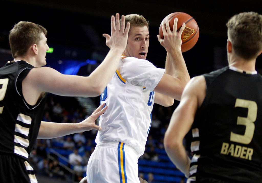 Description of . UCLA forward David Wear, center, pulls down a rebound against Oakland forward Joey Asbury, left, and guard Travis Bader, right, in the second half of an NCAA college basketball game Tuesday, Nov. 12, 2013, in Los Angeles. UCLA won the game 91-60. (AP Photo/Alex Gallardo)