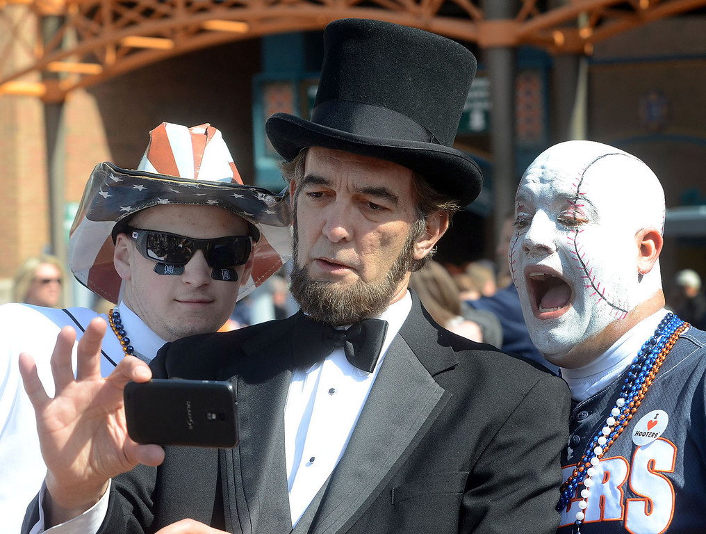 Description of . Abe Lincoln, aka Ron Carley, of Livonia, takes a selfie with some rabid Tigers fans before the start of the Tigers game against Kansas City on Opening Day, Monday March 31, 2014. (Vaughn Gurganian-The Oakland Press)