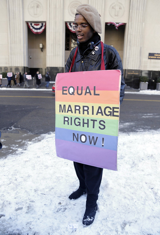 Description of . Duane Gholston, 22, stands outside of Federal Court after closing arguments were made in the trial challenging Michigan's ban on same-sex marriage at the Theodore Levin Federal Court in Detroit Friday Marc. 7, 2014.  Jayne Rowse and April DeBoer have been together for eight years and are raising three adopted children who have special needs. Under Michigan's law, they can't jointly adopt the kids because they're not married, which could cause custody and other legal issues if one of the women died.  (AP Photo/Detroit Free Press, Mandi Wright)  DETROIT NEWS OUT;  NO SALES