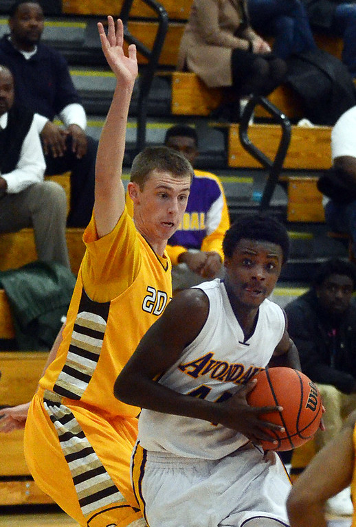 Description of . Avondale's #44 Alex Hodges drives to the basket past Rochester Adams #5 Thomas Girdler during their game at Avondale High School, Tuesday December 11, 2013. (Vaughn Gurganian-The Oakland Press)