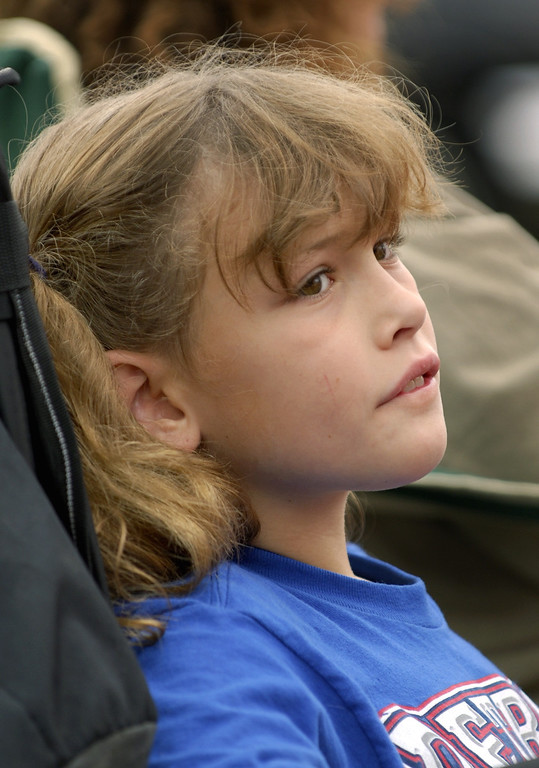 Description of . Destinee Schatz, 10, of Waterford sits back and relaxes as she watches the cars cruise by Saturday at the annual Woodward Dream Cruise.