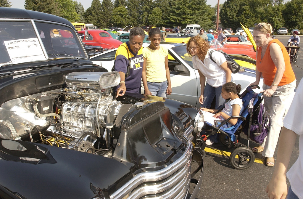 Description of . Special education students got to enjoy the classic cars at the  Crusin' For Kids Kennedy Dream Cruise this morning. This is Olivia Bell (left) and her daughter Tara Bell of Pontiac, and Charmaine Gibson (center)  and her daughter Jazmarae Sanders (seated) of Pontiac with her grandmother Inge Bradley looking on.