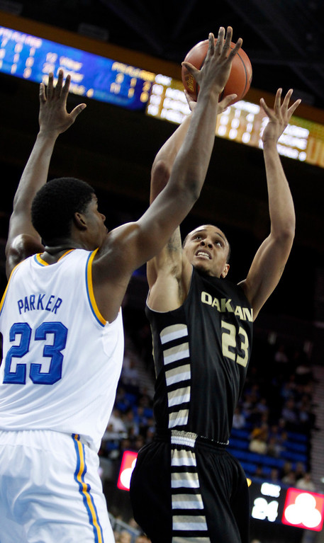 Description of . Oakland forward Tommie McCune, right, shoots over UCLA center Tony Parker, left, in the first half of their NCAA college basketball game Tuesday, Nov. 12, 2013, in Los Angeles. (AP Photo/Alex Gallardo)