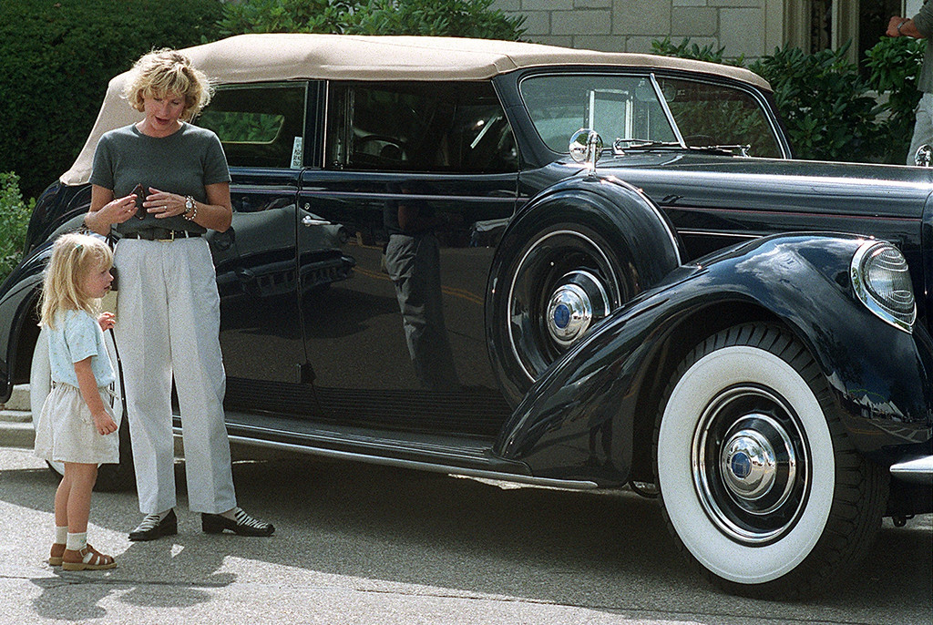 Description of . As her mom Maureen stands by, Ashley Charlebois,3,  probably doesnt realized that she is examining one of only 12 Lincoln Model K\'s ever made. The navy 1937 auto was one of dozens of vintage Ford Motor Company products that ringed Shain Park Friday night as part of a private Revvin\' with Ford event that kicks off Dream Cruise activites this weekend.