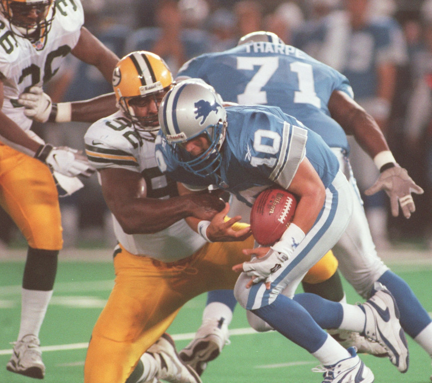 . Detroit Lions quarterback Charlie Batch (right, #10) gets taken down by Green Bay Packers linebacker Reggie White (#92) during second half action, Thursday, October 15, 1998, at the Pontiac Silverdome in Pontiac, Mich.