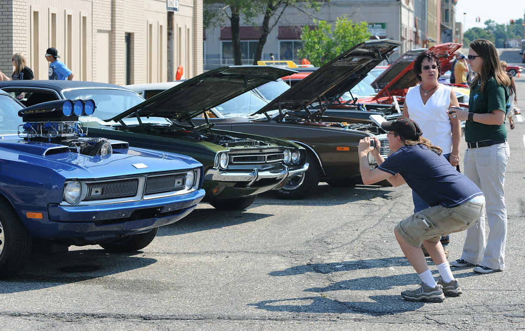 Description of . Shannon Winkler, foreground, of Sylvan Lake, Mich., takes pictures of classic cars during the Dream Cruise, Saturday, August 15, 2009, in Pontiac, Mich.  (The Oakland Press/Jose Juarez)