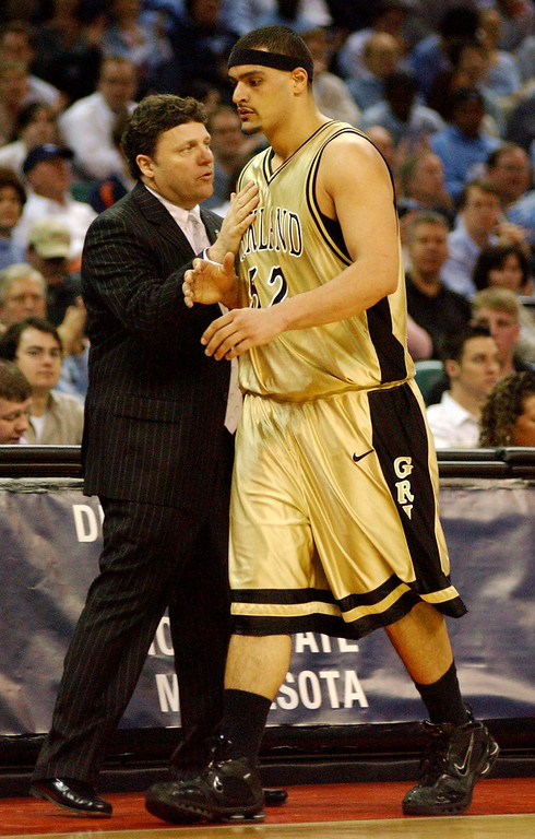 Description of . Oakland University men's basketball head coach Greg Kampe, left, congratulates Cortney Scott for his efforts as Scott is taken out of the game during the final minutes of their game against North Carolina during first half action, Friday, March 18, 2005, at the Charlotte Coliseum in Charlotte, NC.  Oakland lost to North Carolina, 96-68.