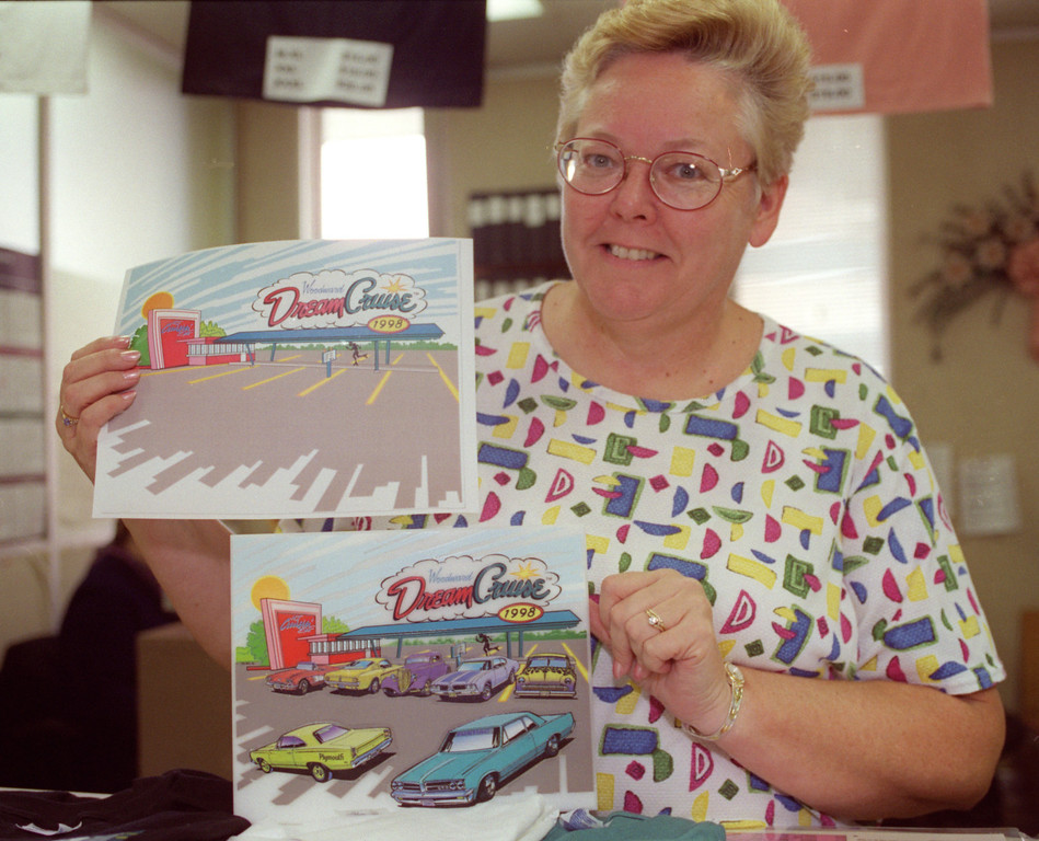Description of . Marsha Mellert , Recreation Supervisor at Ferndale City Hall, shows off the Before/After 7-City Commerative plaque with its colorform-like hotrods, that customers acquire in each city, in the city\'s Dept of Public Services and Recreation, where Dream Cruise merchandise can be bought.