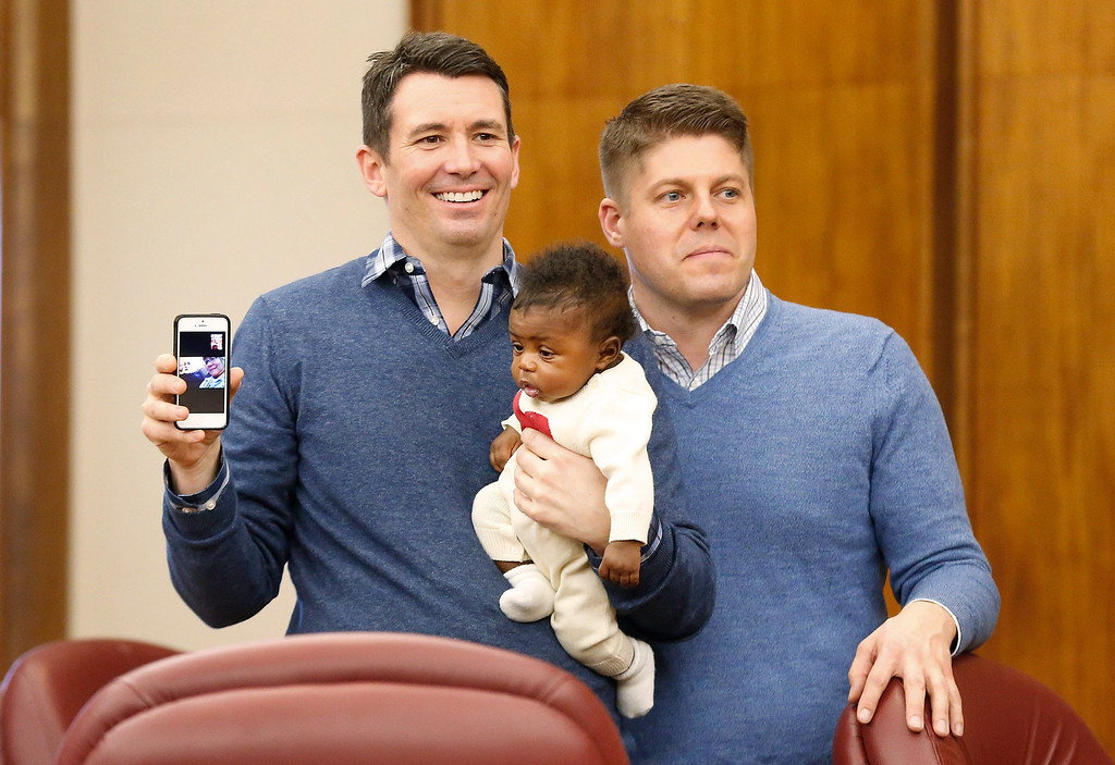 Description of . Jim, left, and Jason Shaffer, hold their daughter Norah, 3 mo., while being married in a group by the Oakland County Clerk in Pontiac, Mich., Saturday, March 22, 2014. A federal judge has struck down Michigan's ban on gay marriage Friday the latest in a series of decisions overturning similar laws across the U.S. Some counties plan to issue marriage licenses to same-sex couples Saturday, less than 24 hours after a judge overturned Michigan's ban on gay marriage. (AP Photo/Paul Sancya)