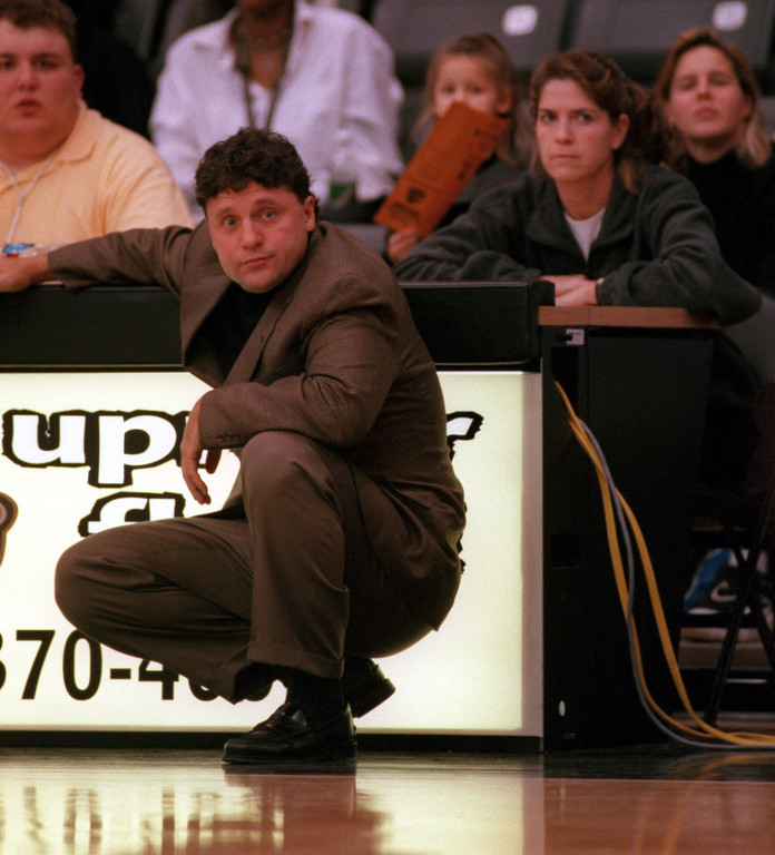 Description of . Oakland University men's basketball head coach Greg Kampe (left) watches the action as women's basketball head coach Beckie Francis (right) observes the action as well, against Team Prestige during second half action, Monday, November 8, 1999.