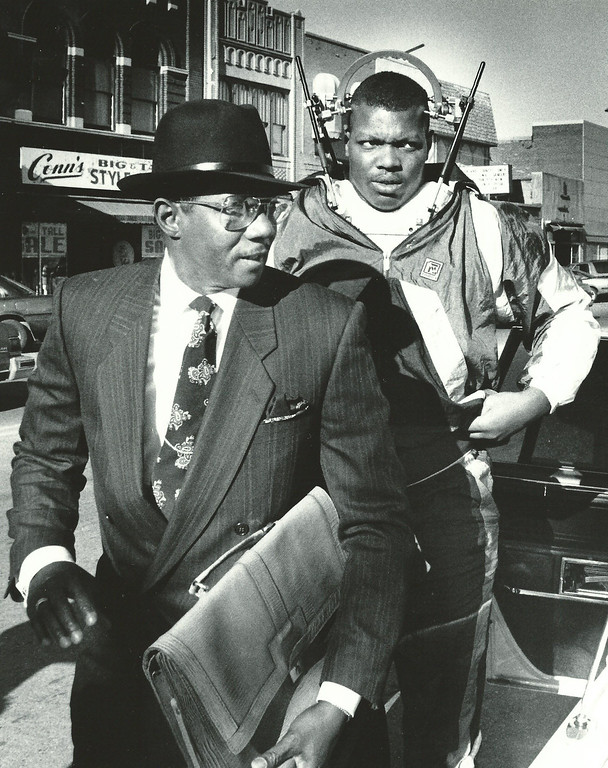 Description of . Former Detroit Lions player Reggie Rogers (wearing halo neck brace) arrives at 50th District Court in Pontiac in Nov. 1988 via limousine with attorney Elbert Hatchett. The Oakland Press/file photo