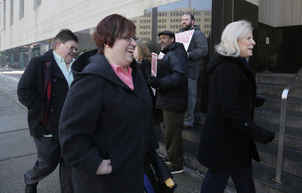Description of . Jayne Rowse, left, and her partner April DeBoer and DeBoer's mother Wendy DeBoer pass protestors and supporters before closing arguments in their trial challenging Michigan's gay-marriage ban at the Theodore Levin Federal Court in Detroit Friday March 7, 2014. Michigan's ban on same-sex marriage was approved by voters in 2004.  Detroit federal Judge Bernard Friedman is not expected to make a decision Friday.  (AP Photo/Detroit Free Press, Mandi Wright)  DETROIT NEWS OUT;  NO SALES