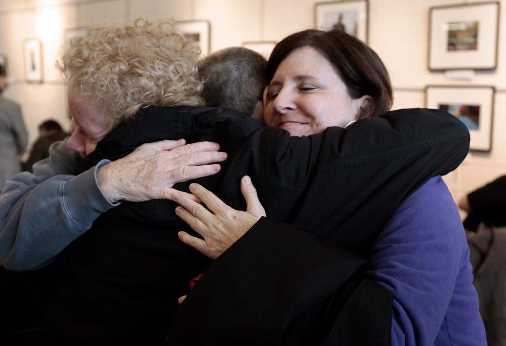 Description of . Susan Horowitz, left, and Judy Valenti, right, hug a friend in Ferndale, Mich., Friday, March 21, 2014. A federal judge has struck down Michigan's ban on gay marriage Friday the latest in a series of decisions overturning similar laws across the U.S. April DeBoer and Jayne Rowse, two nurses who've been partners for eight years, claimed the ban violated their rights under the U.S. Constitution. (AP Photo/Paul Sancya)