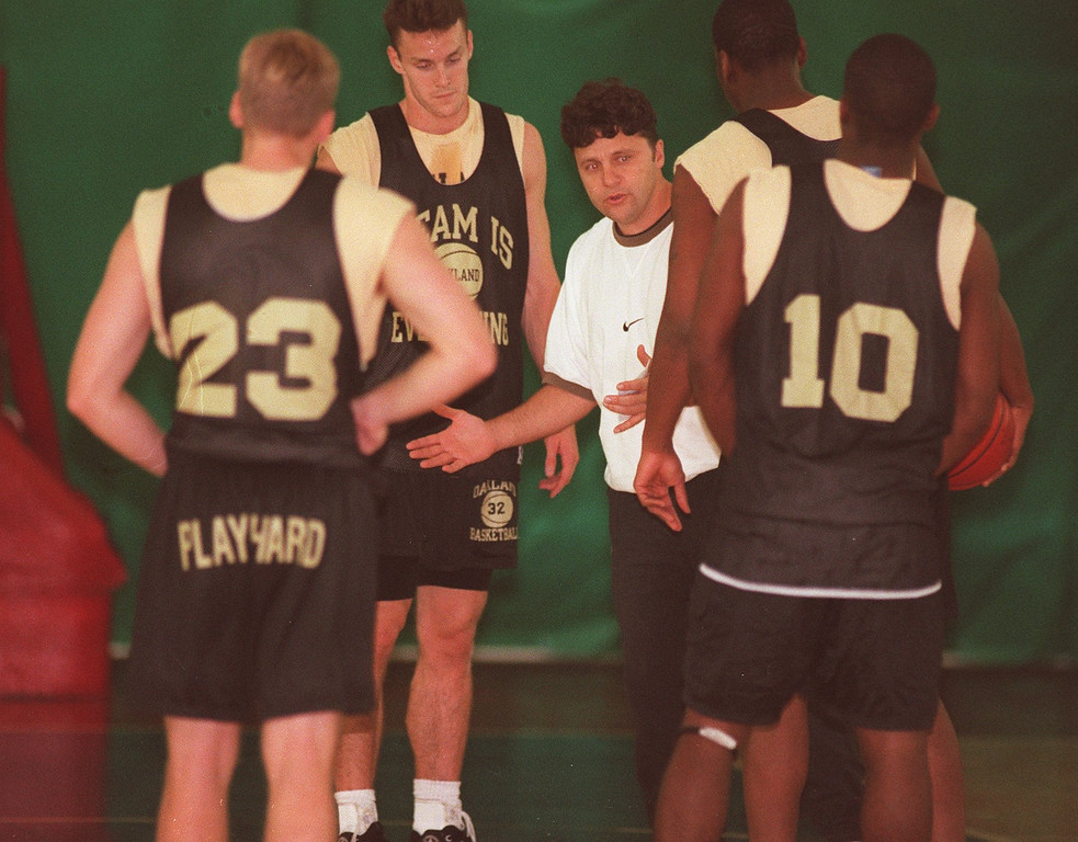 Description of . O.U. mens basketball head coach Greg Kampe talks with some of his players during practice.
