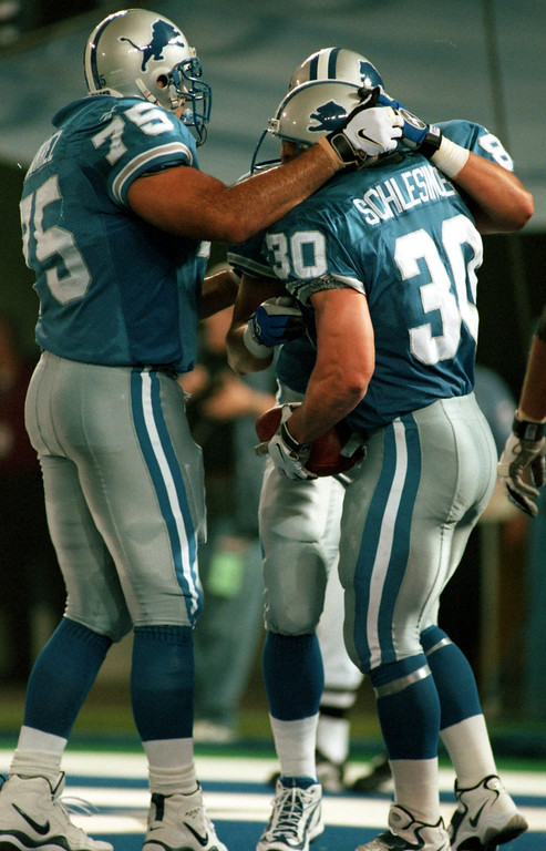 . Detroit Lions players congratulate Cory Schlesinger (30) after he scored an early first quarter touchdown against the Arizona Cardinals during their preseason home opener.