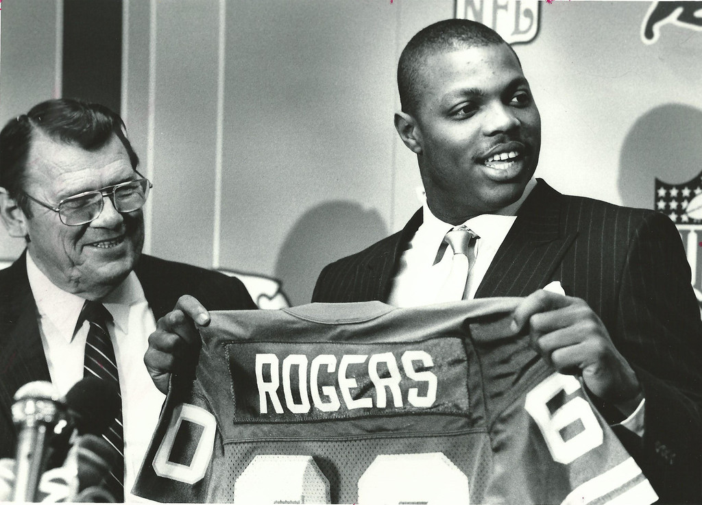 Description of . Former Lions player Reggie Rogers, drafted No. 7 overall by Detroit in the 1987 NFL Draft, shows off his new No. 60 jersey with then-Lions general manager Russ Thomas (left). Oakland Press file photo