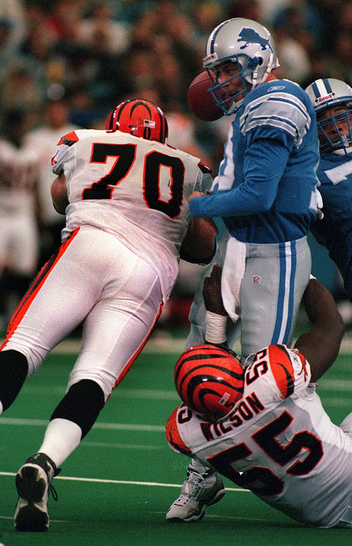 . Evading a tackle by Bengal DT #70 Glen Steele (left), Detroit Lions quarterback Charlie Batch gets ripped down by Cincinnati DE Reinard Wilson #55  (right)  during the Lions 31-27 loss at the Silverdome Sunday. Batch was sacked four times.