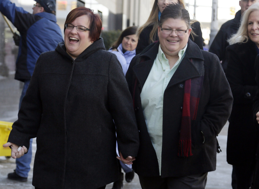 Description of . April DeBoer, left, and her partner Jayne Rowse hold hands after closing arguments were made in their trial challenging Michigan's ban on same-sex marriage at the Theodore Levin Federal Court in Detroit Friday Marc. 7, 2014.  Rowse and DeBoer have been together for eight years and are raising three adopted children who have special needs. Under Michigan's law, they can't jointly adopt the kids because they're not married, which could cause custody and other legal issues if one of the women died.  (AP Photo/Detroit Free Press, Mandi Wright)  DETROIT NEWS OUT;  NO SALES