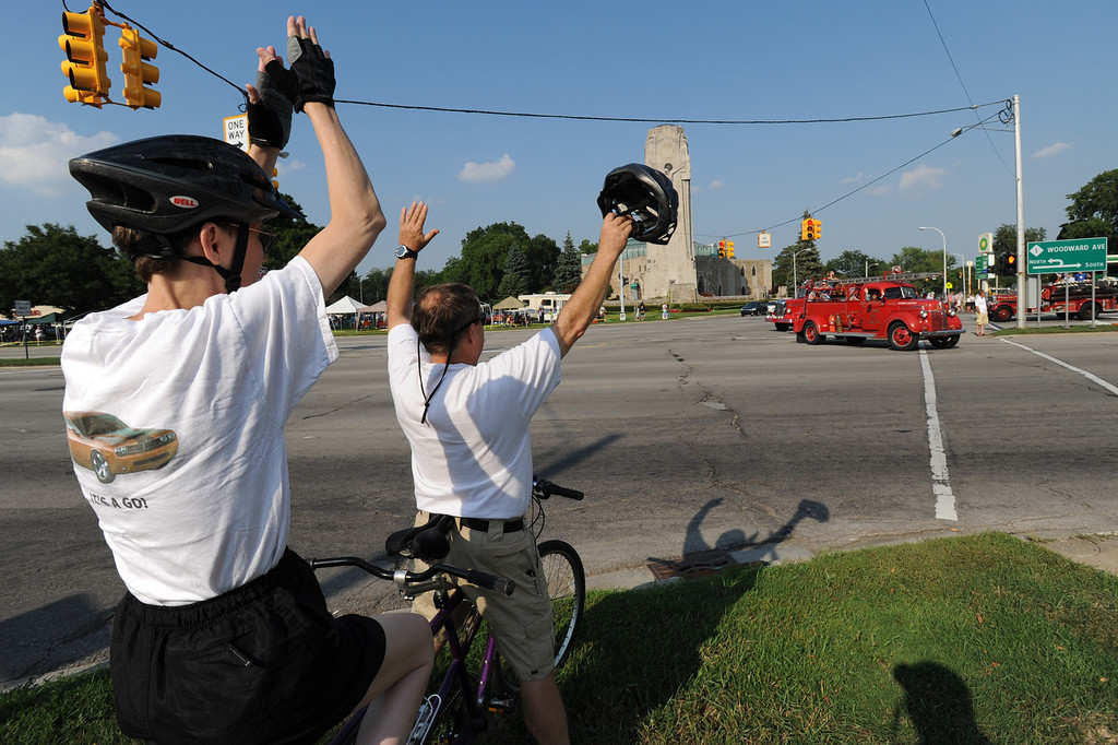 Description of . Jenny Cole, far left, and Gary Cole of Berkley, Mich., show enthusiastic support as the Lights & Sirens Cruise traveled from Ferndale all the way into the Royal Oak/Berkley area, as the caravan makes a u-turn on 12 Mile Road, to head back south on Woodward towards Ferndale again.  Later, the city of Berkley's own Cruisefest would take place along 12 Mile Road .  Photo taken on Friday, August 14, 2009, in Berkley, Mich.  (The Oakland Press/Jose Juarez)