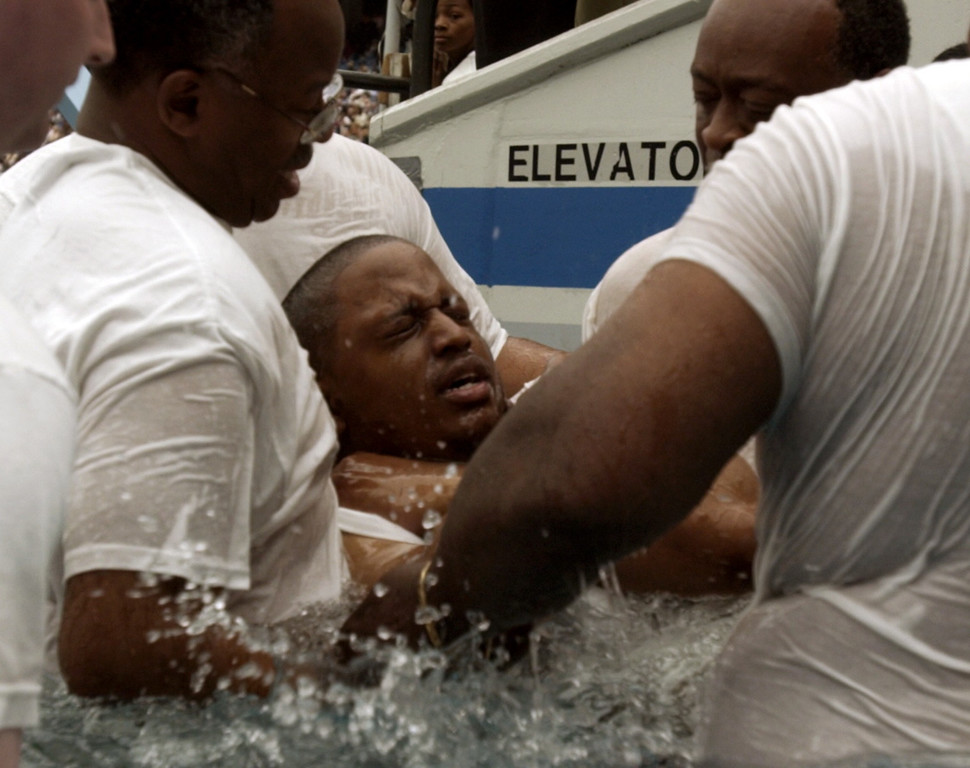Description of . Held tightly by several volunteers, Johnny Ayers is baptized in a pool of water at the annual Zealous Kingdom Proclaimers district convention Saturday at the Silverdome.  Ayers, who cannot walk and was in a wheelchair, was carried into the water by the volunteers, so that he could participate in this most important ritual. Dozens of guests were baptized Saturday at the convention.