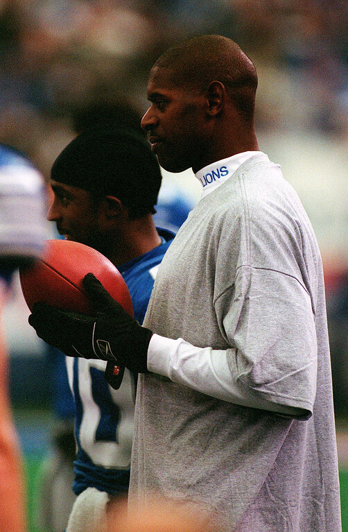 . Football in hand, Injured Detroit Lions wide receiver Herman Moore watches the action of Sunday\'s 27-24 loss to the Tennessee Titans from the sidelines at the Silverdome.