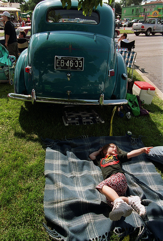 Description of . A sleepy Samantha Jensen, 4, tries to nap on a blanket behind her grandpa\'s 1942 Willys during the Woodward Dream Cruise saturday afternoon.